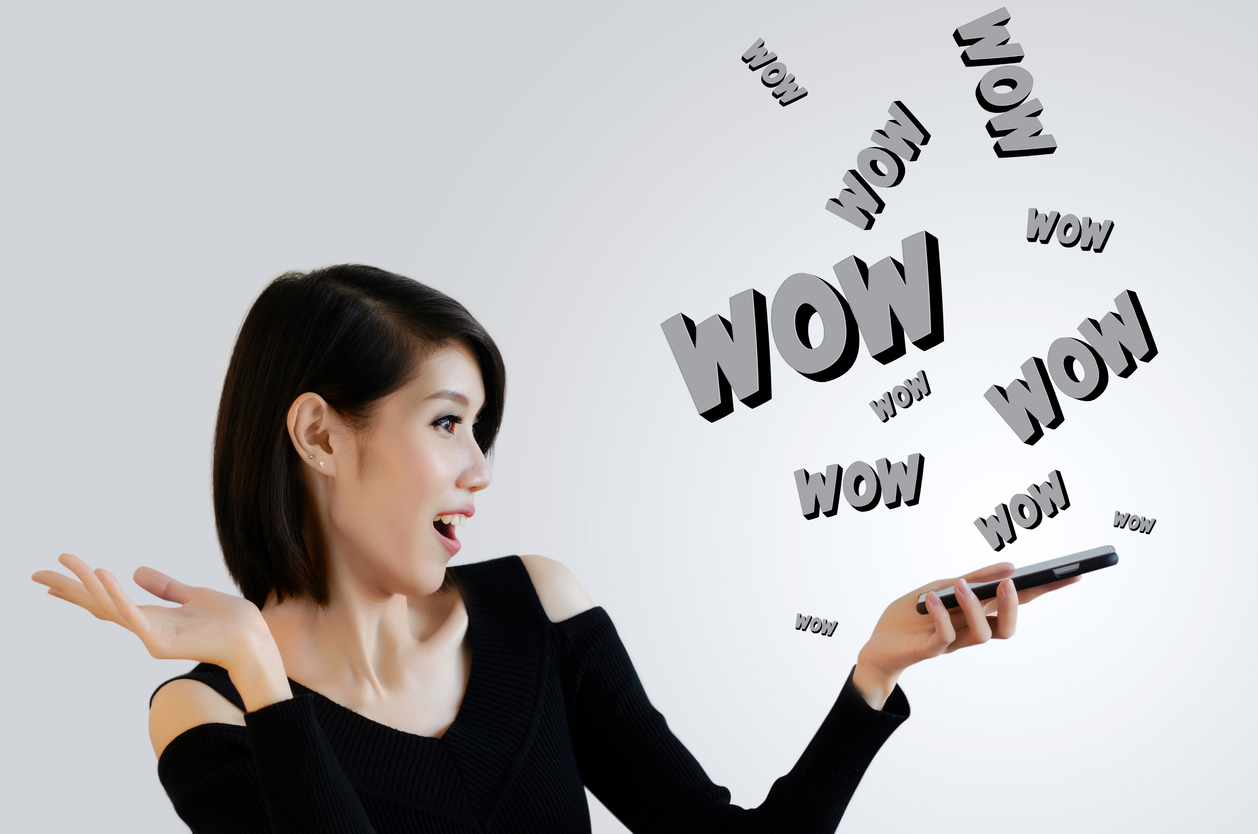 Excited woman looking happily and surprisingly at mobile phone