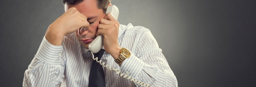 Overwhelmed businessman in white shirt and tie having a headache during a stressful phone conversation. Tired thoughtful businessman with one hand on his forehead taking a tedious phone call.